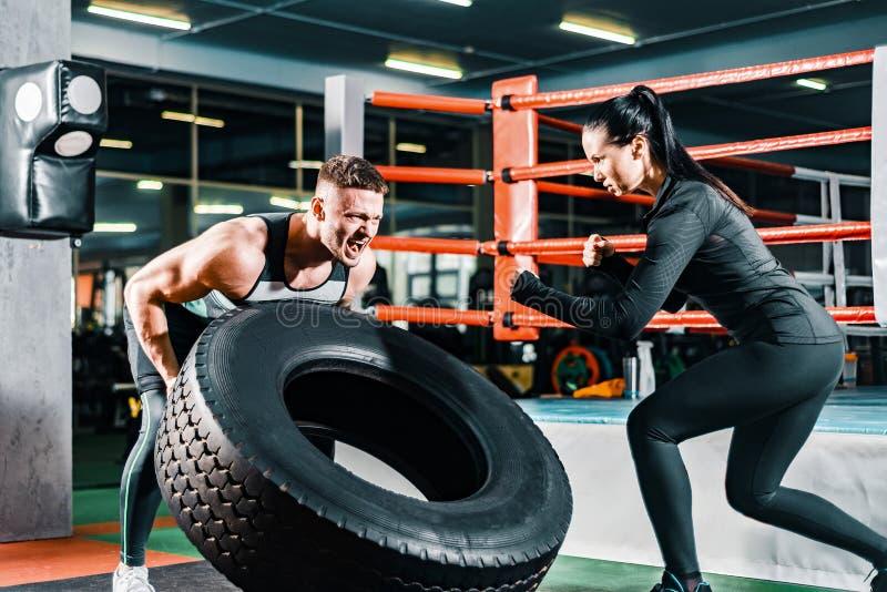 Muskul?ser Mann, der einen Frachtbus in der Turnhalle dr?ckt weiblicher Trainer regt Sportkerl an Konzeptmotivation, zum von Bem? stockbilder