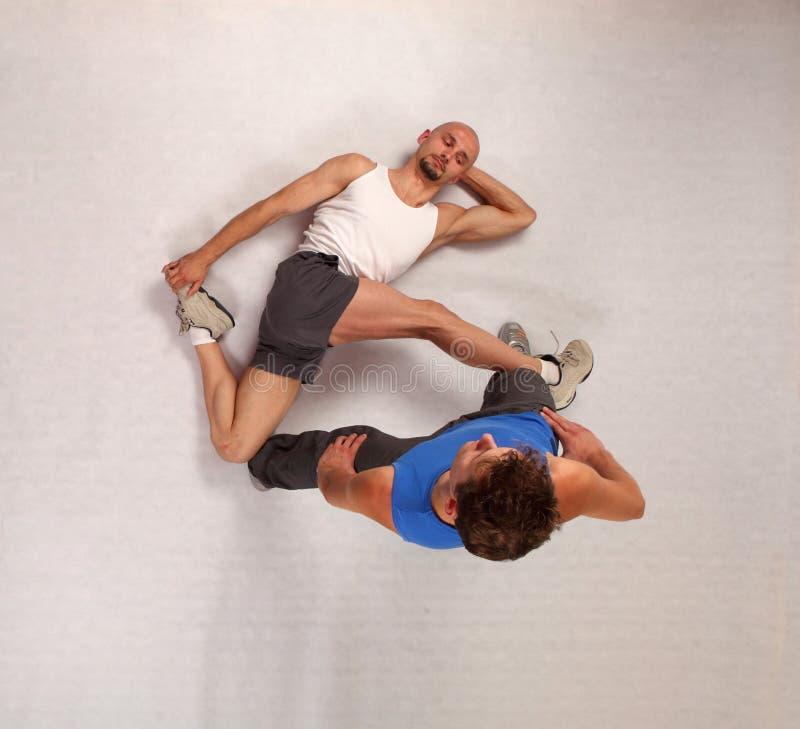 Muskulöser Mann, der mit persönlichem Kursleiter ausdehnt lizenzfreie stockbilder