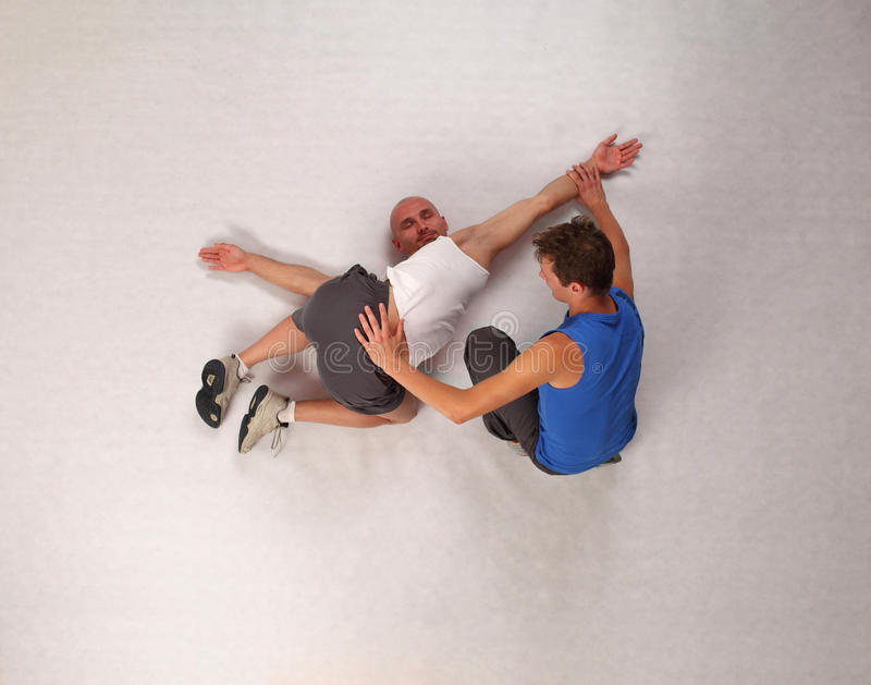 Muskulöser Mann, der mit persönlichem Kursleiter ausdehnt stockfoto