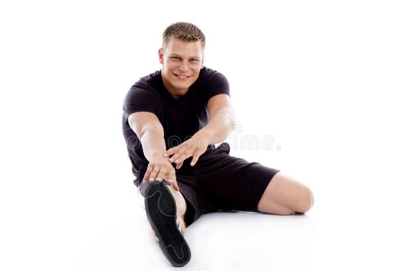 Muskulöser Mann, der seine Fahrwerkbeine und Hände ausdehnt lizenzfreie stockfotografie