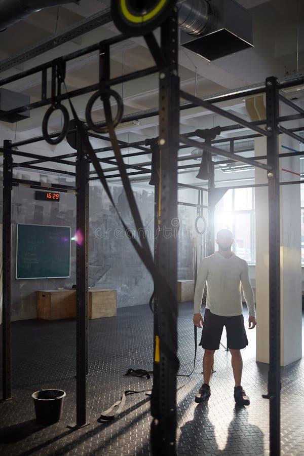 Muskulöser Mann in der sonnenbeschienen Turnhalle stockbilder
