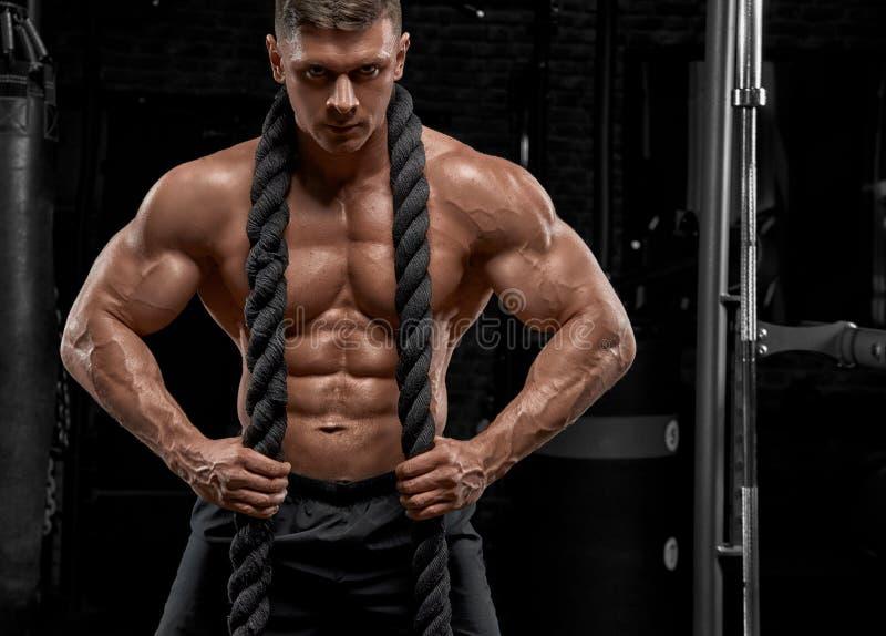 Muskulöser Mann, der in der Turnhalle tut Übungen ausarbeitet lizenzfreie stockfotos