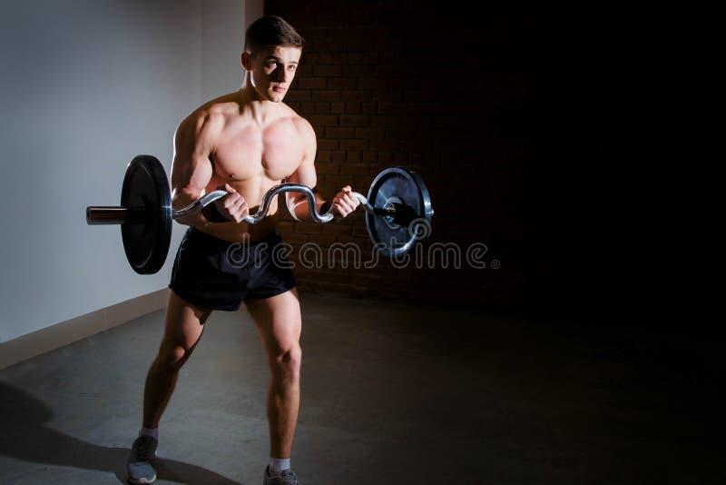 Muskulöser Mann, der in der Turnhalle tut Übungen mit Barbell, starke männliche nackte Torso-ABS ausarbeitet lizenzfreie stockfotos