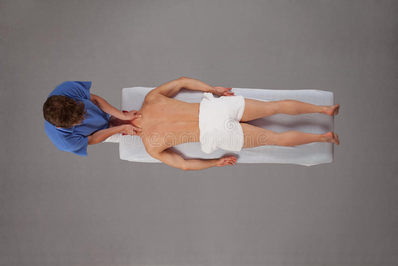Muskulöser Mann, der vom Therapeuten massiert wird stockfoto