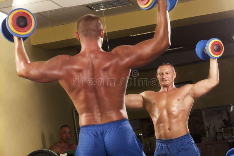 Muskulöser Mann, der Weightlifting in der Gymnastik tut stockfotos