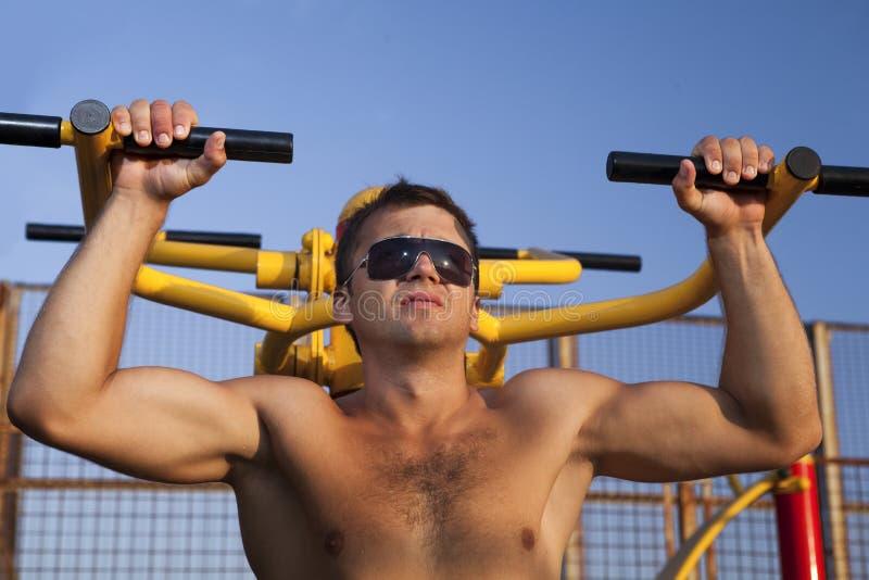 Muskulöser Mann, der Weightlifting tut stockbild