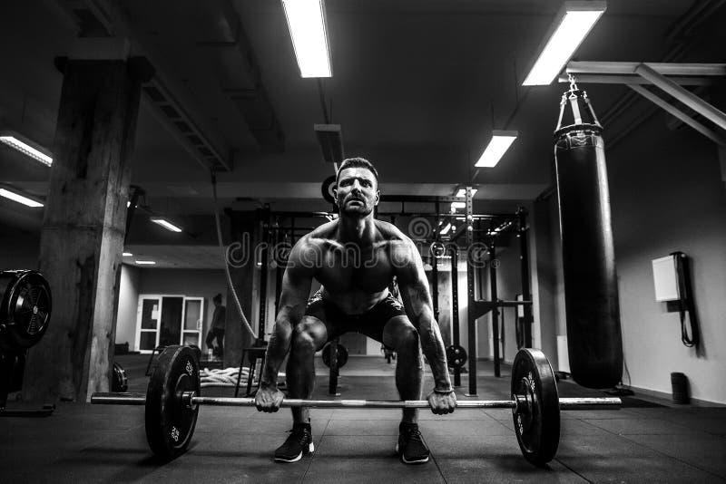 Muskulöser Mann an einer crossfit Turnhalle, die einen Barbell anhebt stockfotos