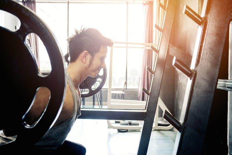 Muskulöser Mann errichtete den Athleten, der in der Turnhalle und im Gewichtheben ausarbeitet lizenzfreies stockfoto