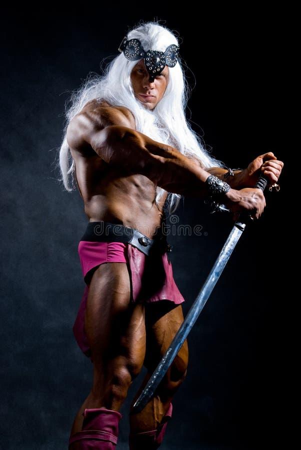 Muskulöser Mann-Krieger mit dem weißen langen Haar, das eine Klinge anhält stockfoto