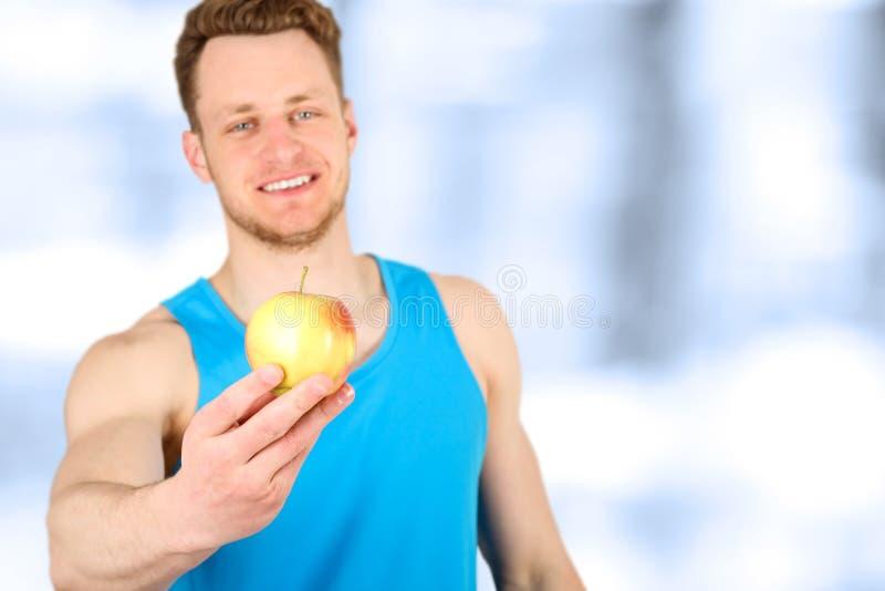 Muskulöser Mann mit den Armen, die einen Apfel geben lizenzfreie stockbilder