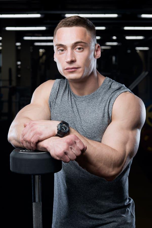 Muskulöser Mann mit den großen Armen wirft im grauen Hemd auf stockfotos