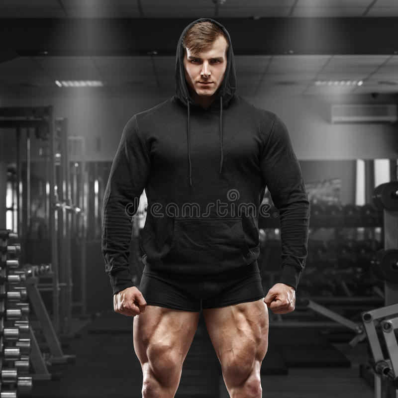 Muskulöser Mann mit den Muskelbeinen in der Turnhalle Starker Mann im schwarzen Hoodie mit großen Viererkabeln stockfotografie