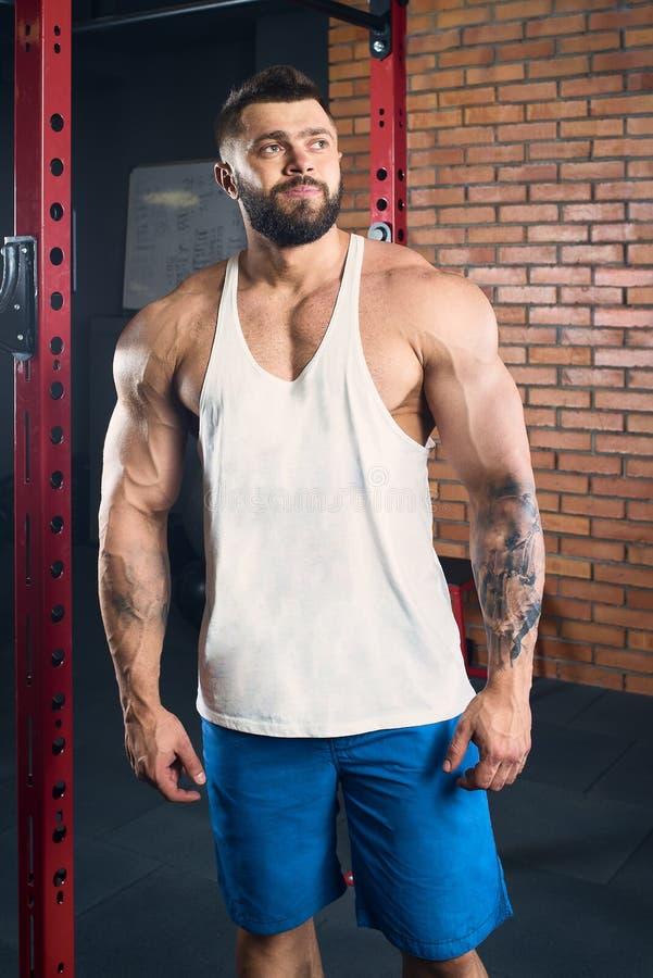 Muskulöser Mann mit den Tätowierungen und Bart, die in einem schwarzen Trägershirt stehen und blaue kurze Hosen in der Turnhalle lizenzfreie stockfotografie