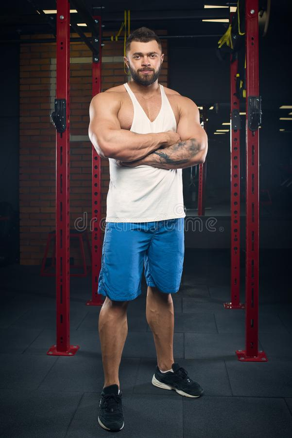 Muskulöser Mann mit den Tätowierungen und Bart, die in einem weißen Trägershirt aufwerfen und blaue kurze Hosen in der Turnhalle lizenzfreie stockbilder