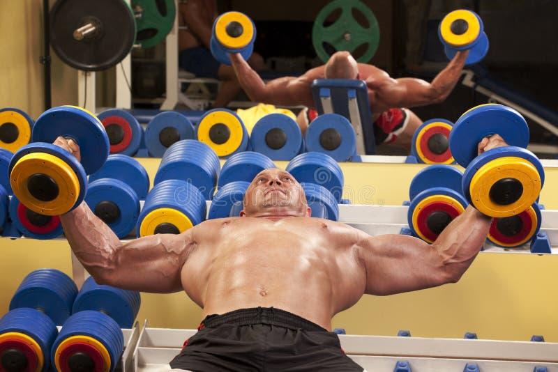 Muskulöser Mann mit Gewichten eines Stabes bei der Handausbildung stockfotos