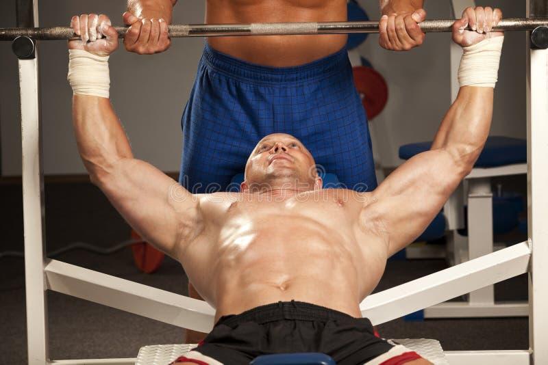 Muskulöser Mann mit Gewichten eines Stabes bei der Handausbildung stockbild