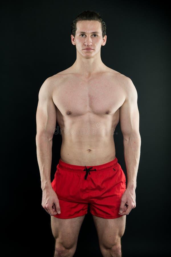 Muskulöser Mann mit starkem Körper Sport und Eignung E Eignungs-Mann, der in der Turnhalle trainiert paßsitz lizenzfreies stockbild