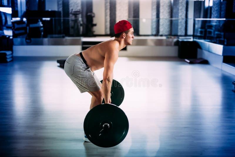 Muskulöser Mann, Sonderkommandos von crossfitter und Eignungstrainer, der an der Turnhalle ausarbeitet und hintere exercices mach lizenzfreies stockbild