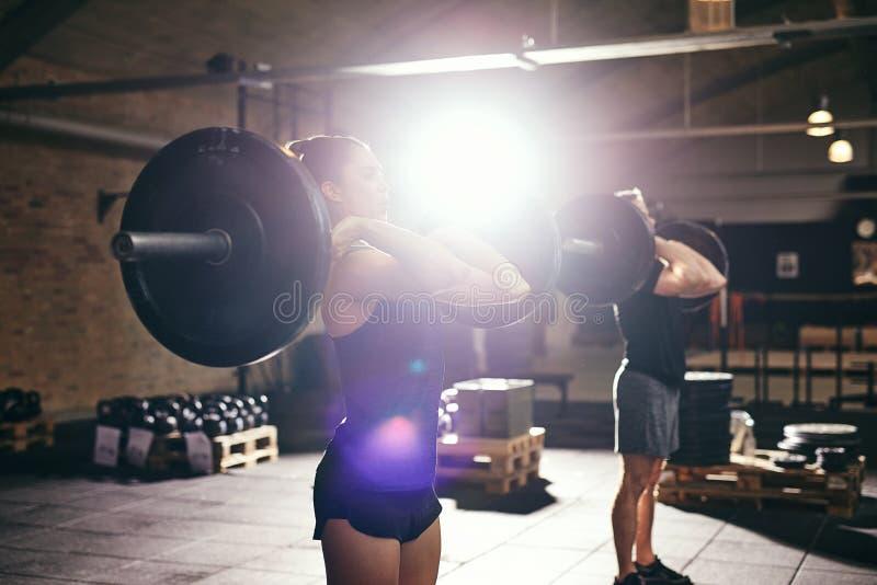 Muskulöser Mann und Frau, die Barbellübung tut stockbilder
