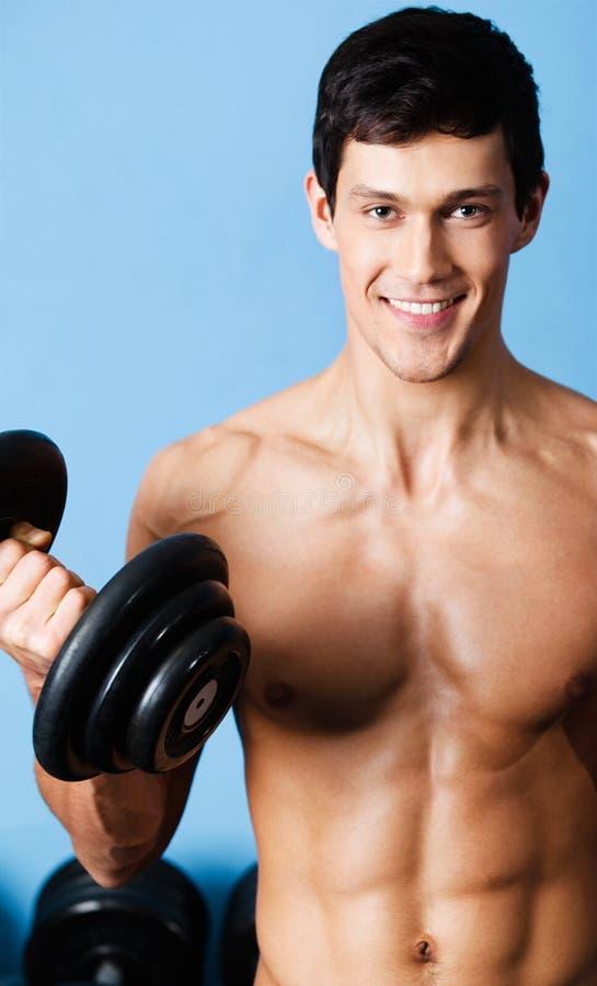 Muskulöser Mann verwendet seinen Dumbbell stockfotografie