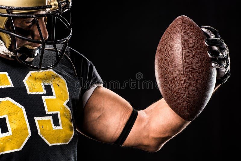 Muskulöser Spieler des amerikanischen Fußballs im schützenden Sportkleidungsschauen stockfotografie