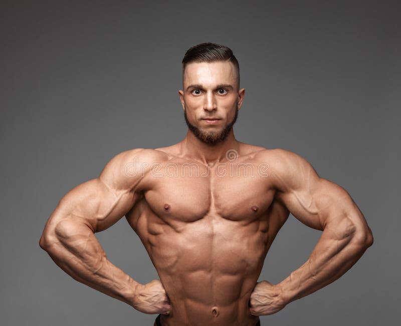 Muskulöser super-er-hoh waagerecht ausgerichteter gut aussehender Mann, der auf grauem Hintergrund aufwirft lizenzfreie stockbilder