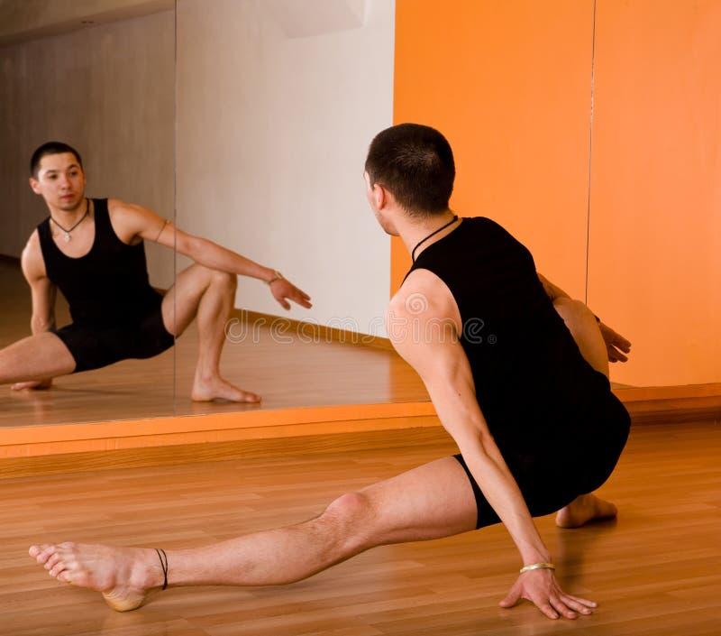 Muskulöser Tänzer, der in der Halle aufwirft lizenzfreie stockfotos