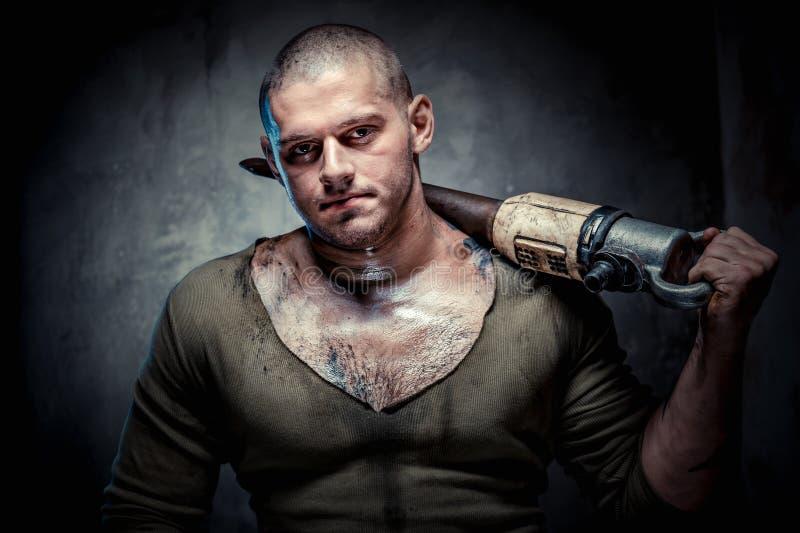 Muskulöser tätowierter Mann mit Jackhammer stockbild