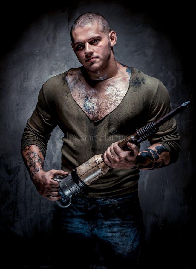 Muskulöser tätowierter Mann mit Jackhammer stockfotos