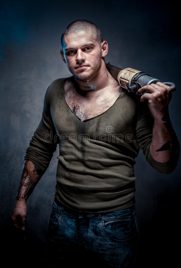 Muskulöser tätowierter Mann mit Jackhammer lizenzfreies stockfoto