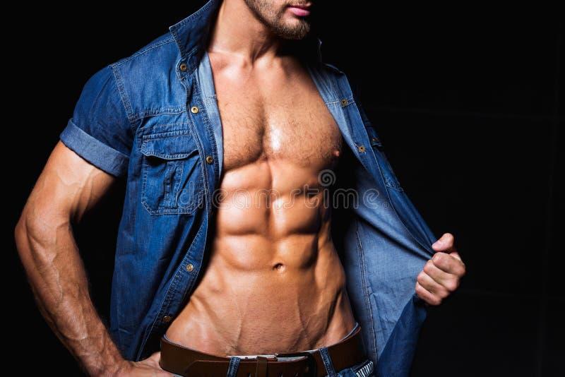 Muskulöser und sexy Körper des jungen großen Stücks in den Jeans stockfoto