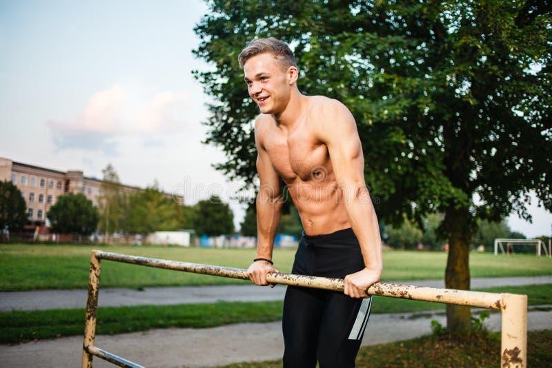 Muskulöser Zug des jungen Mannes ups die horizontale Stange Straßentraining lizenzfreies stockbild