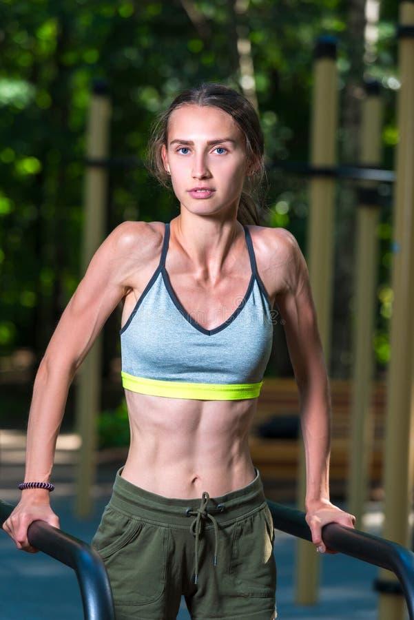 muskulöses starkes Mädchen während des Sports in der Frischluft im Park stockbild