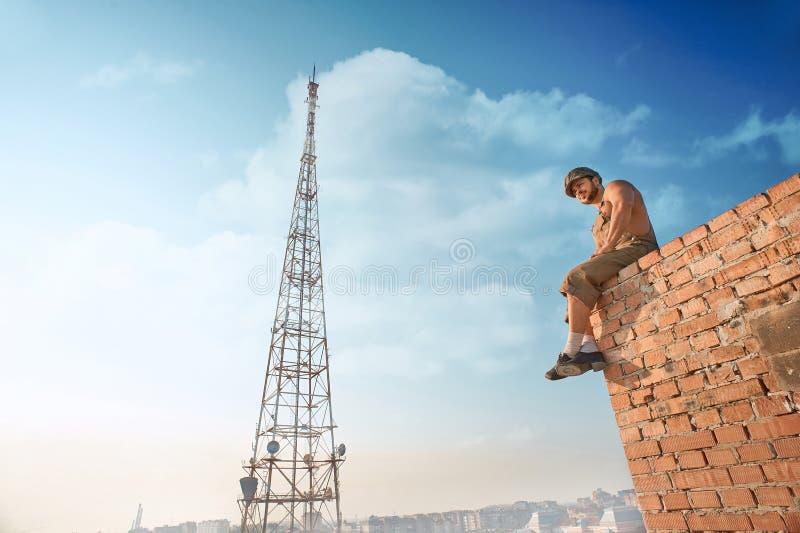 Muskulöst byggmästareanseende på tegelstenväggen på höjdpunkt arkivfoto