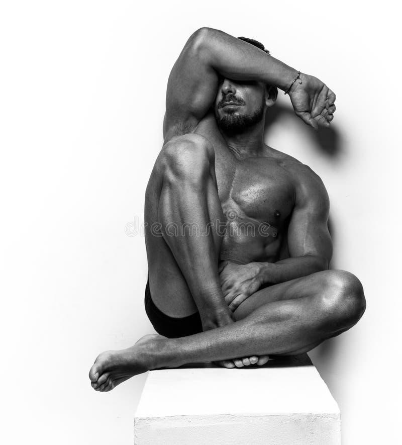 Muskulöst mansammanträde på vit royaltyfria foton