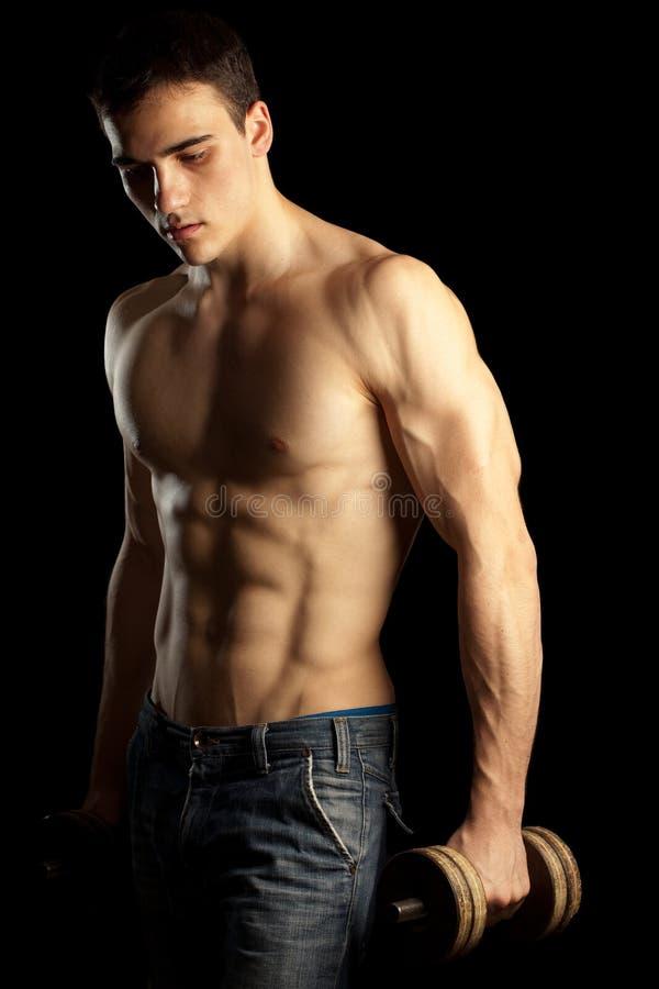 muskulöst sexigt för dumbellman arkivfoton