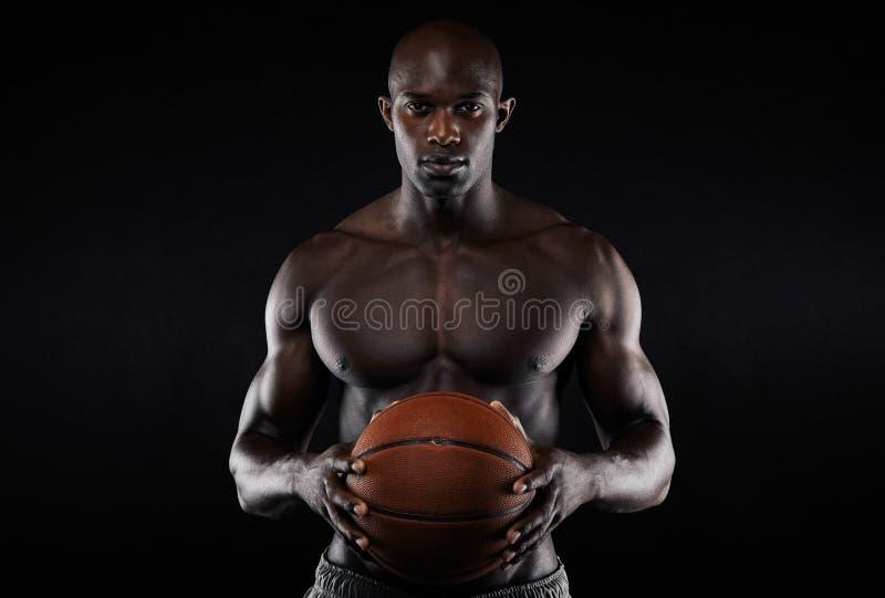 Muskulöst shirtless innehav för ung man en basket royaltyfria bilder