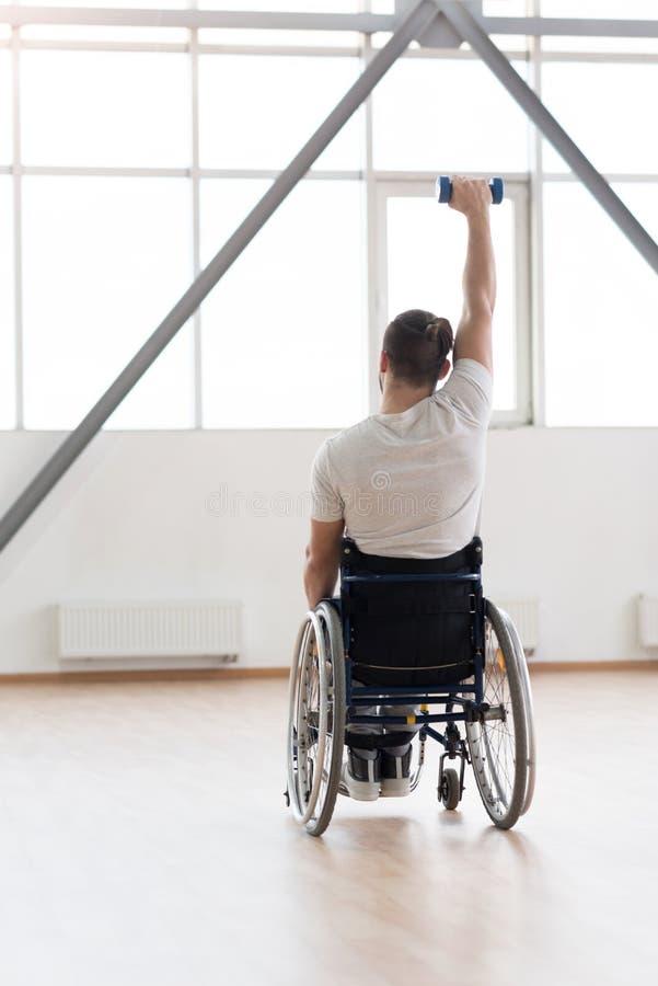 Muskulöst ungt ogiltigt öva med vikter i idrottshall royaltyfria foton
