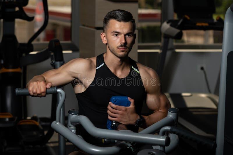 Muskul?s man som g?r tungvikt?vningen f?r baksida arkivbilder