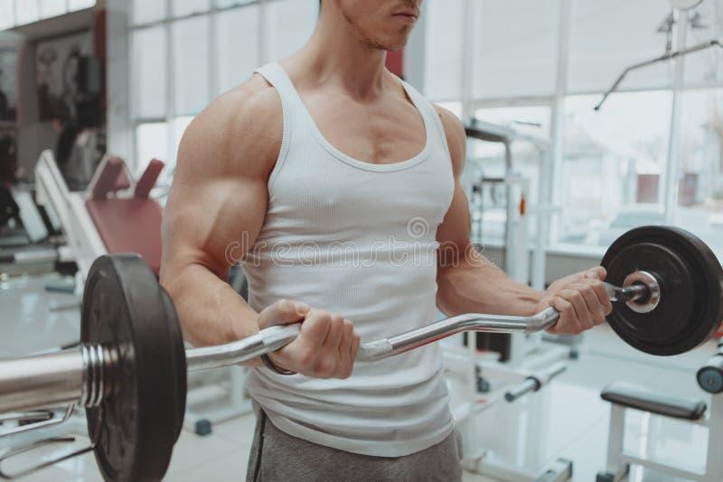 Muskul?s man som utarbetar p? idrottshallen arkivfoto