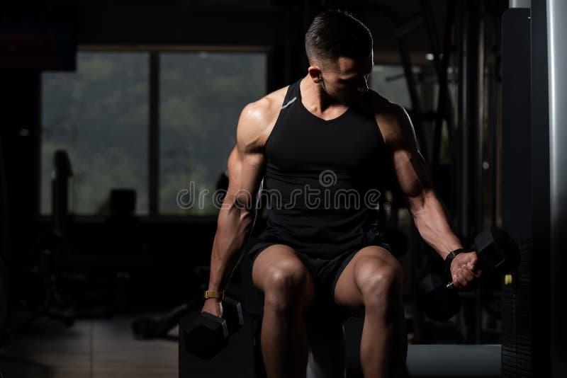 Muskul?s man som ?var biceps med hanteln royaltyfri bild