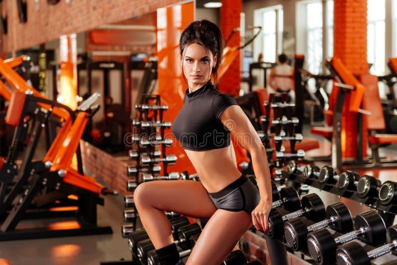 Muskul?s ung kvinna med den h?rliga kroppen som g?r ?vningar med hanteln royaltyfria bilder
