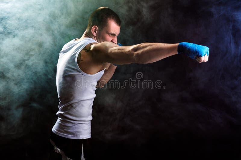 Muskul?ses kickbox oder muay thail?ndischer K?mpfer, die im Rauche lochen stockbild