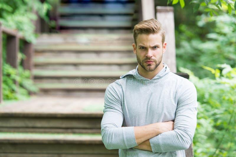 Muskul?st och s?kert Muskulös man på sommardag Den idrotts- grabben som håller muskulösa armar korsade på, parkerar trappa stilig arkivfoto
