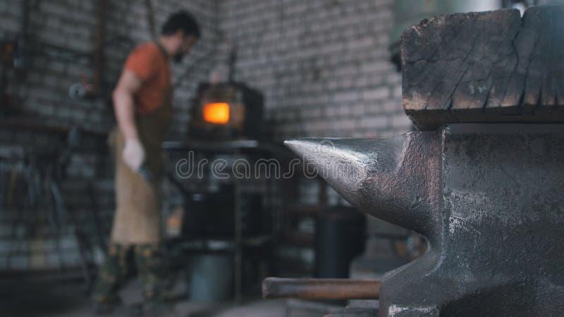 Muskularmens - de smid smeedt binnen dichtbij oven stock foto