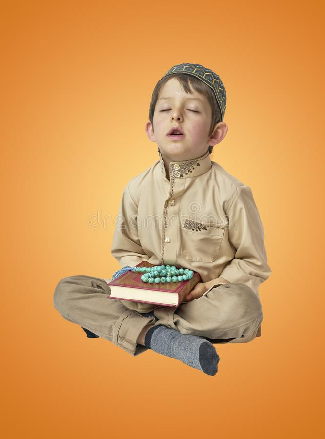 Little arabic boy praying and holding Quran with prayer beads. Muslim Arabic boy praying on colorful background stock photos