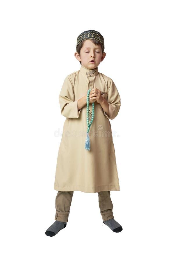 Little muslim boy praying and holding prayer beads on white background. Muslim Arabic boy praying on white background stock photography