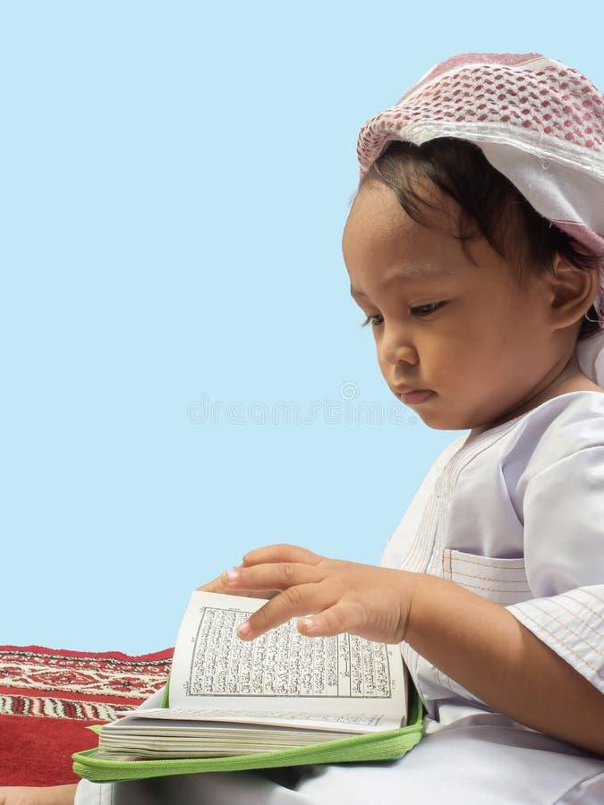 Muslim boy in a dress  reading the Koran , isolate background. Muslim boy in a dress reading the Koran , isolate background stock images