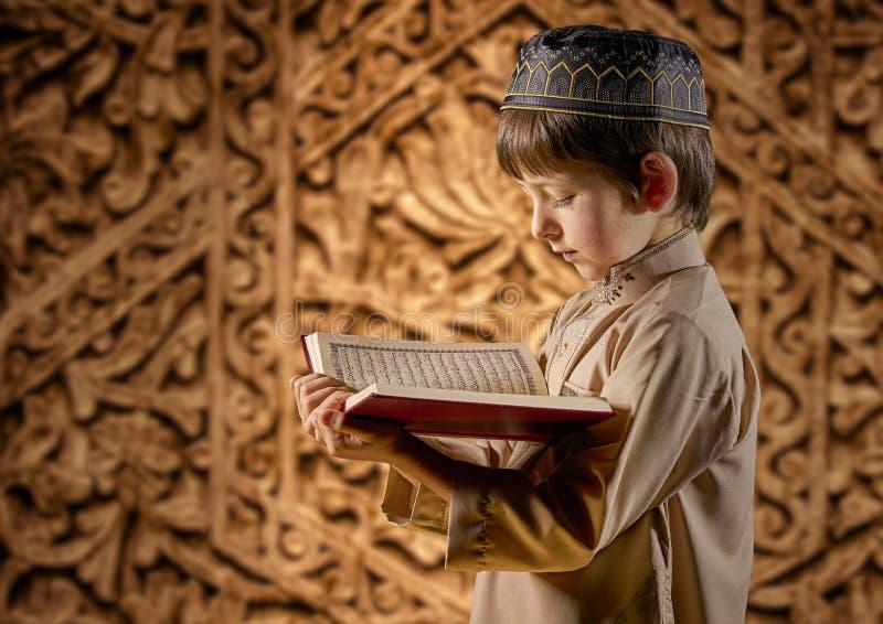 Muslim Boy Lees het heilige islamitische boek Koran stock foto's