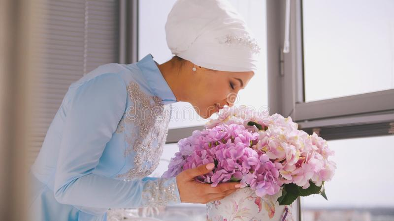 Muslim bride in blue wedding dress for nikah, smelling flowers royalty free stock images